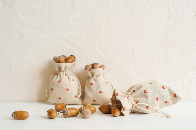 Autumn composition with acorns in linen bags. autumn, fall concept. copy space