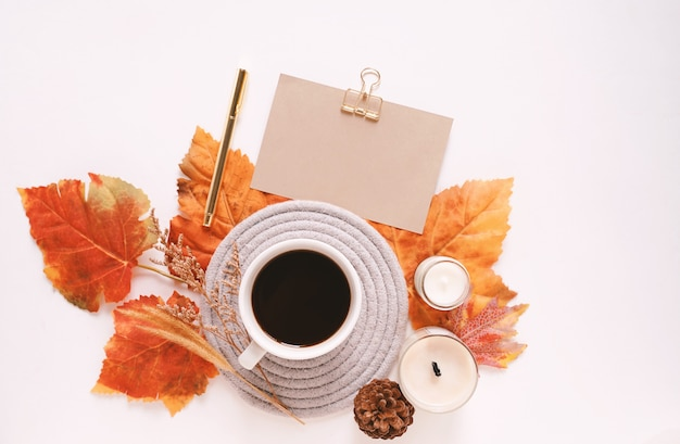 Autumn composition with candle, coffee cup and greeting card