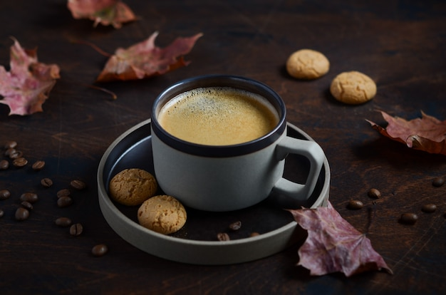Autumn composition with cup of coffee and autumn leaves on dark wooden table
