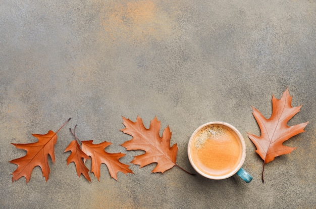 Autumn composition with cup of coffee and autumn leaves on stone or concrete background flat lay top view copy space