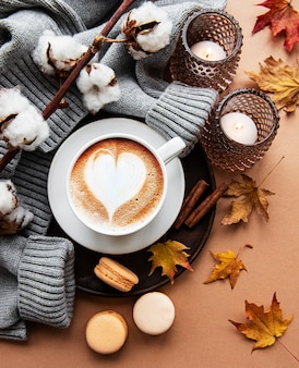Autumn composition with cup of coffee, warm blanket, decorative striped pumpkins, candles and autumn leaves