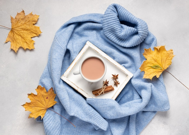 Autumn composition with cup hot cocoa on cozy knitted sweater with yellow leaves warming drinks
