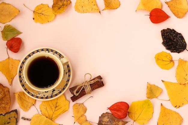 Осенняя композиция с чашкой кофе и рамкой из палочек корицы из осенних листьев, вид сверху