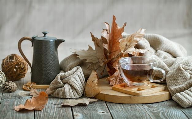 Composizione autunnale con una tazza di tè e dettagli decorativi di comfort domestico.