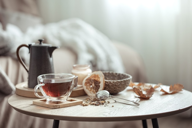 Autumn composition with a cup of tea, a teapot and autumn home decor details on a blurred background.