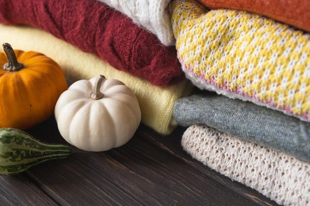さまざまなニットセーターとカボチャの秋の構成。ハロウィーン、感謝祭の日または季節の背景。