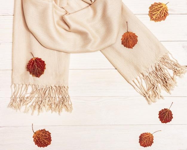 アスペンとパステルベージュのスカーフの乾燥した葉と秋の構成