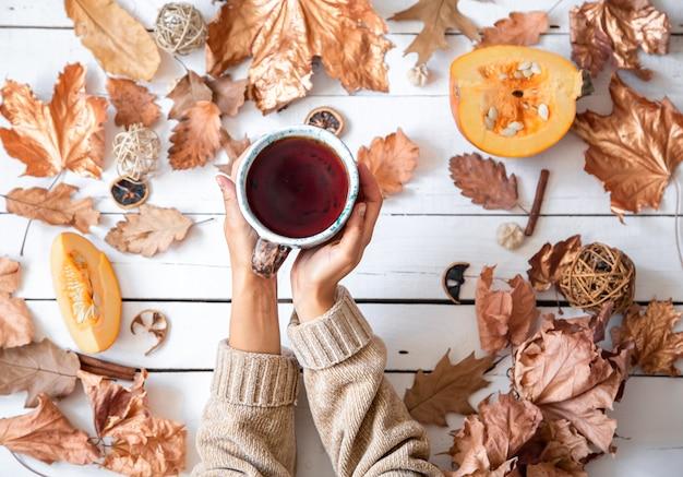 Осенняя композиция с сухими листьями и женскими руками, держащими плоскую чашку чая.