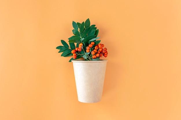 Осенняя композиция с экологически чистым бумажным стаканчиком и гроздью рябины на оранжевом фоне. минималистичный, стильный, креативный осенний натюрморт. плоская планировка, копия пространства.