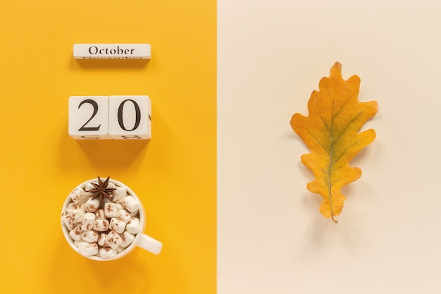 Autumn composition with hot cocoa, date and autumn leaf