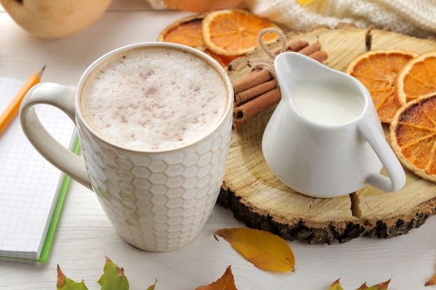 ホットコーヒー、暖かいスカーフ、白い木製のテーブルの上の黄色の葉と秋の組成