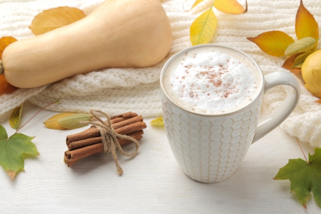 Autumn composition with hot coffee, a warm scarf and yellow leaves on a white wooden table