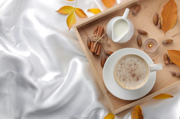 Autumn composition with hot coffee and yellow leaves on a tray on the bed. view from above