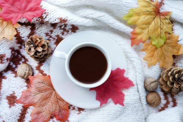 스카프, 견과류, 잎을 넣은 뜨거운 커피 한 잔으로 가을 구성. 아늑한 아침, 편안함, 휴식, 우울, 가을 날씨, 집의 개념.