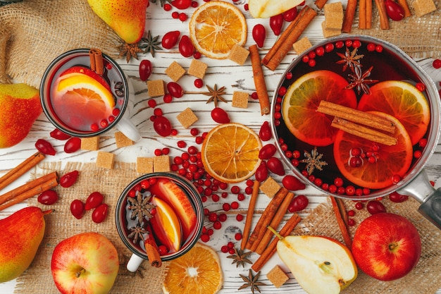 Autumn composition with hot mulled wine and spices on wooden background