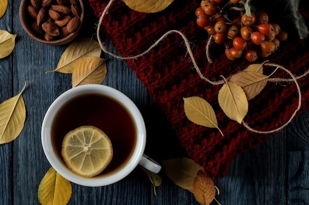 紺色の木製テーブルに熱いティーナッツベリーと秋の黄色の葉を使った秋の構図。上面図