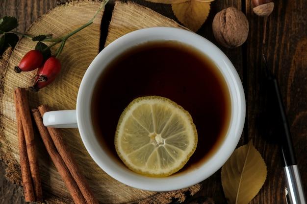 Осенняя композиция с горячим чаем на деревянной подставке, корицей, шиповником, орехами на коричневом деревянном столе. вид сверху