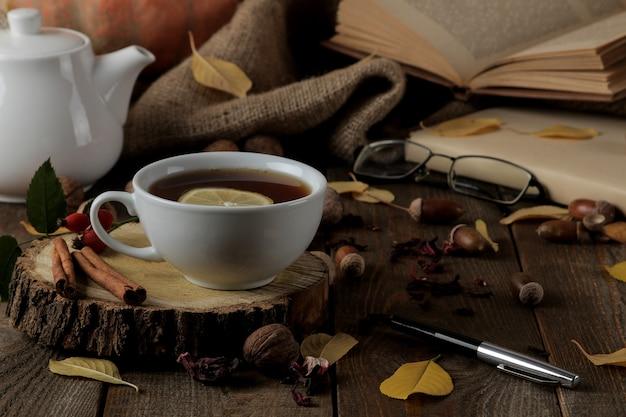 Осенняя композиция с горячим чаем на деревянной подставке, корица, шиповник, орехи на коричневом деревянном столе