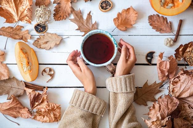 Осенняя композиция с листьями и чашкой чая на белой стене вид сверху.