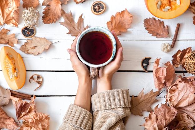 Осенняя композиция с листьями и чашкой чая, вид сверху.