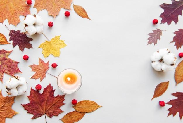 秋の葉と白い背景の上のろうそくの組成