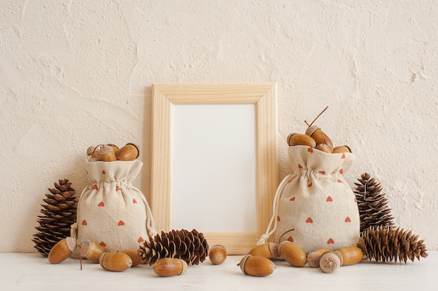 Autumn composition with mock up frame, acorns  in linen bags and pine cones