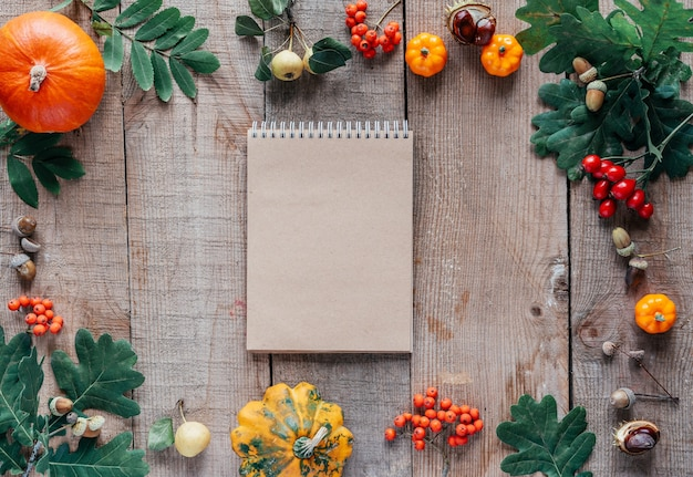Autumn composition with notebook leaves pumpkins and acorns on wooden background