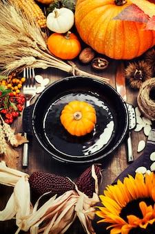 Осенняя композиция с тыквой на тарелке и осенними украшениями. концепция дня благодарения