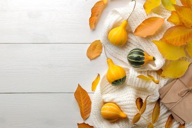 Осенняя композиция с тыквами и теплым шарфом на белом деревянном столе.