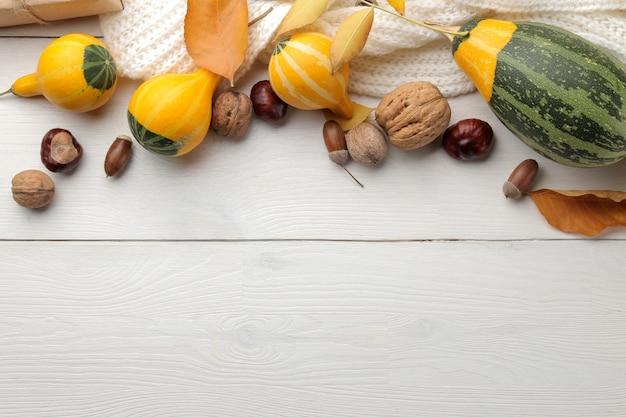 Осенняя композиция с тыквами и желтыми листьями и теплым шарфом.