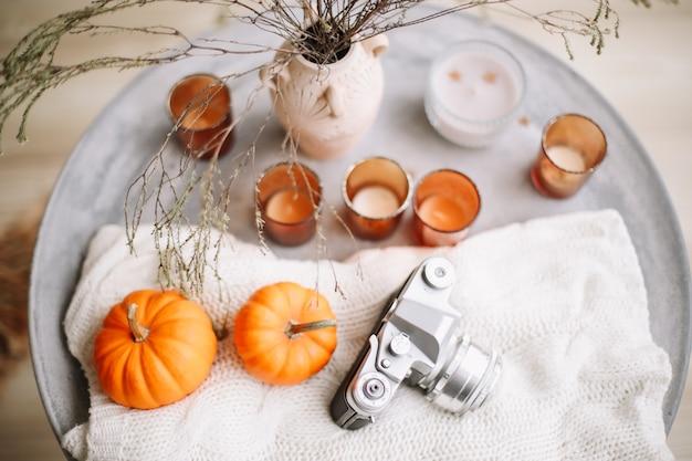 Осенняя композиция с тыквами, свечами, книжкой и сухоцветами, с теплым пледом Premium Фотографии
