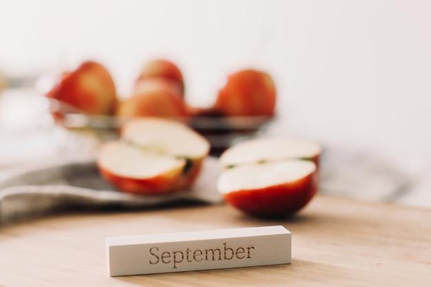 Осенняя композиция с красными яблоками и словом сентябрь на белом фоне