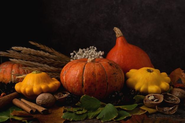Осенняя композиция с сезонными овощами, тыквой, опавшими листьями, дарами природы и шишками