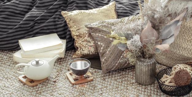 ティーポットとお茶、枕、居心地の良い家の装飾のドライフラワーと秋の構成。