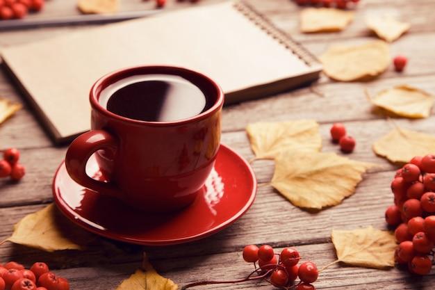 空白のノートブック、鉛筆、赤いカップのコーヒーと美しい赤いカエデの葉を持つワークスペースと秋の組成物。トップビュー、フラットレイアウト、ヴィンテージ調。秋リラックスコンセプト