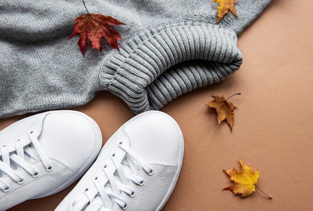 秋の構成。女性は茶色の表面に服を作ります。セーター、スニーカー、乾燥した葉。秋、秋のコンセプト。フラットレイ、上面図、コピースペース