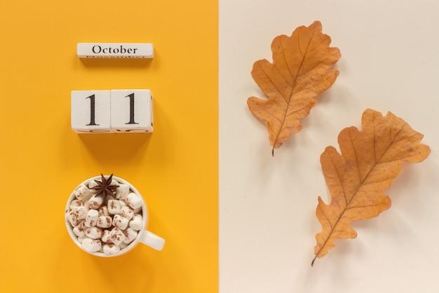 秋の構成。木製のカレンダー、マシュマロと黄色いベージュの背景に黄色い紅葉とココアのカップ。上面図フラットレイモックアップコンセプトこんにちは9月。
