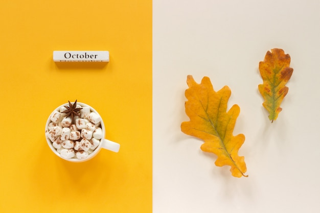 Autumn composition. wooden calendar month october, cup of cocoa with marshmallows and autumn leaves