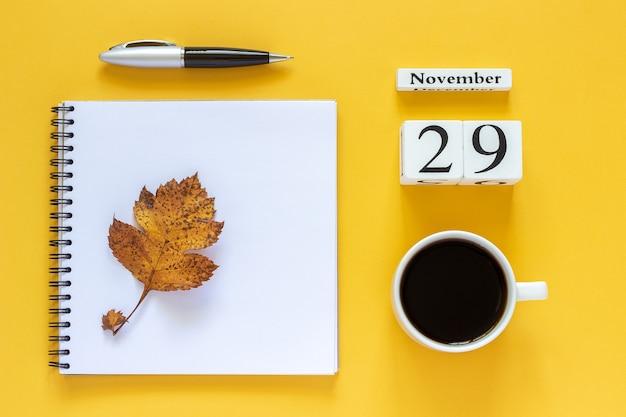 秋の構成。木製のカレンダー11月29日コーヒー、ペンと黄色の背景に黄色のオークの葉と空の開いたメモ帳。上面図フラットレイモックアップコンセプトこんにちは11月