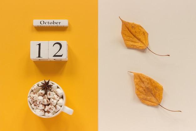 秋の構成。木製のカレンダー10月12日、黄色いベージュの背景にマシュマロと黄色い紅葉のココアのカップ。上面図フラットレイモックアップコンセプトこんにちは9月。