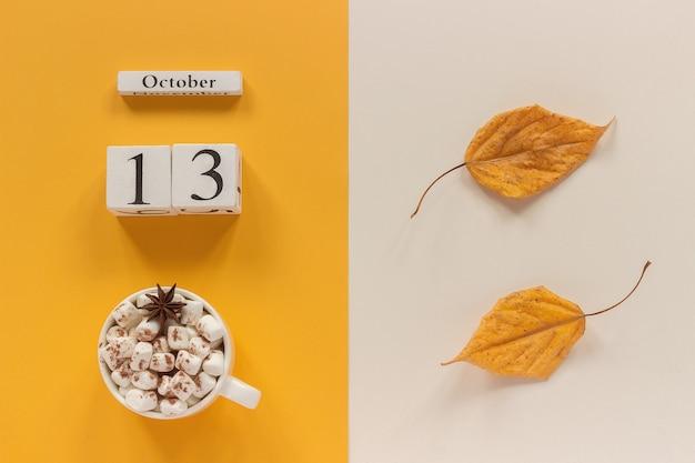 Осенняя композиция. деревянный календарь 13 октября, чашка какао с зефиром и желтыми осенними листьями на желто-бежевом фоне. вид сверху концепция макета плоской планировки привет, сентябрь.