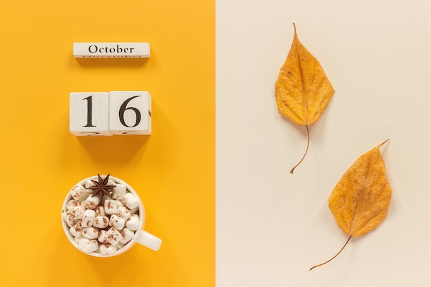 Осенняя композиция. деревянный календарь 16 октября, чашка какао с зефиром и желтыми осенними листьями на желто-бежевом фоне. вид сверху концепция макета плоской планировки привет, сентябрь.
