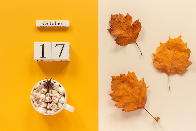 秋の構成。木製のカレンダー10月17日、マシュマロと黄色のベージュの背景に黄色の紅葉とココアのカップ。上面図フラットレイモックアップコンセプトこんにちは9月。
