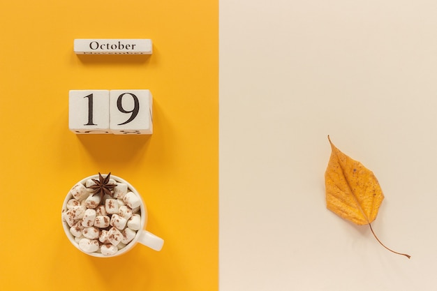 Autumn composition. wooden calendar october 19, cup of cocoa with marshmallows and yellow autumn leaves on yellow beige background. top view flat lay mockup concept hello september.