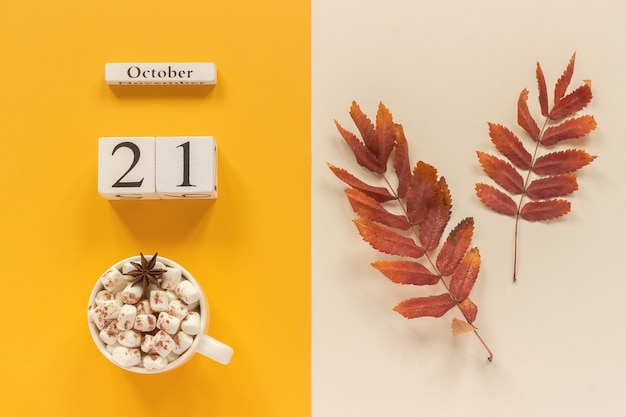 Autumn composition. wooden calendar october 21, cup of cocoa with marshmallows and red yellow autumn leaves on yellow beige background. top view flat lay mockup concept hello september.