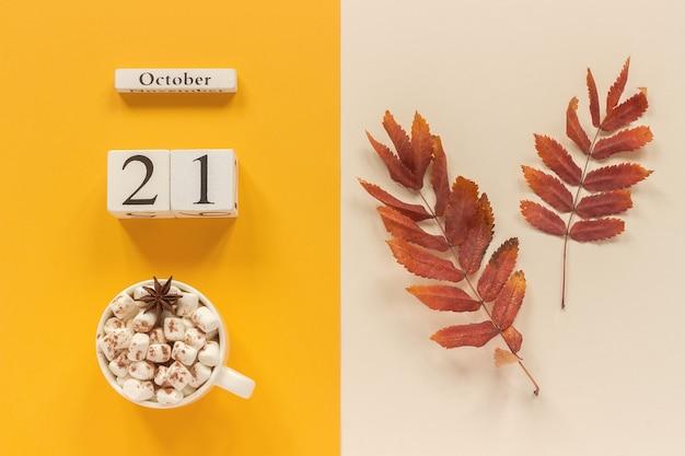Осенняя композиция. деревянный календарь 21 октября, чашка какао с зефиром и красно-желтыми осенними листьями на желто-бежевом фоне. вид сверху концепция макета плоской планировки привет, сентябрь.