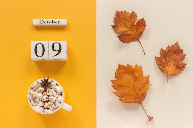 秋の構成。木製のカレンダー10月9日、黄色いベージュの背景にマシュマロと黄色い紅葉のココアのカップ。上面図フラットレイモックアップコンセプトこんにちは9月。