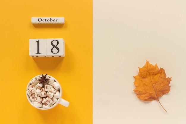 秋の構成。木製のカレンダー10月、黄色いベージュの背景にマシュマロと黄色い紅葉のココアのカップ。上面図フラットレイモックアップコンセプトこんにちは9月。