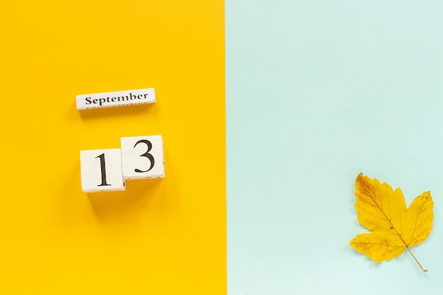 Autumn composition wooden calendar september 13 and yellow autumn leaves on yellow blue background