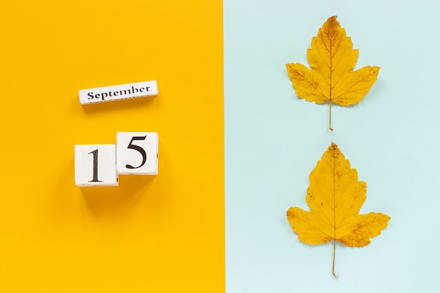 Autumn composition. wooden calendar september 15 and yellow autumn leaves on yellow blue background.